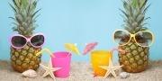 Twee ananassen met zonnebril op het strand aan het drinken