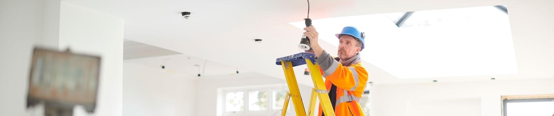 een elektricien is bezig met de bedrading in een huis